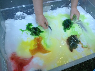 adding ice to goop, adding ice to slime, ic ein slime messy play, ice dinosaurs, kids messy playing in garden, melting colourful ice animals, ice slime tray