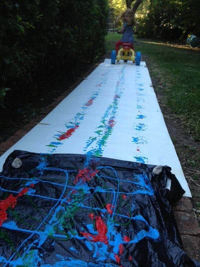 bike paint tracks, cycling in paint, preschooler messy play, very messy paint idea, trikes in paint, cycling on paper, messy bike tracks, bike tracks in paint, kids craft, kids art
