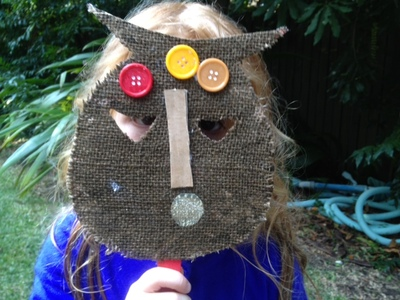 sticking buttongs on african mask, collage african mask, kids gluing collage mask, fun kids craft, mask ideas for kids, making masks with kids