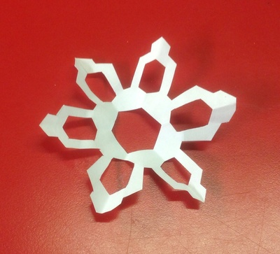 Cutout snowflake, red table, white paper