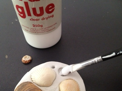 gluing shell onto shell encrusted clay decoration