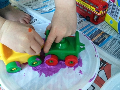 messy play painting with toy car