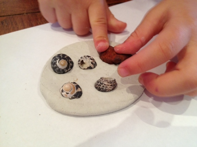 placing shells on clay disc  - Shell Encrusted Clay Decorations