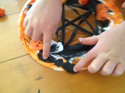 preschooler sticking on to paper plate, bat, orange black halloween craft, ideas for teachers, ideas for kindy halloween, kindy art, kindy craft, preschooler art idea halloween, preschooler craft ideas Halloween