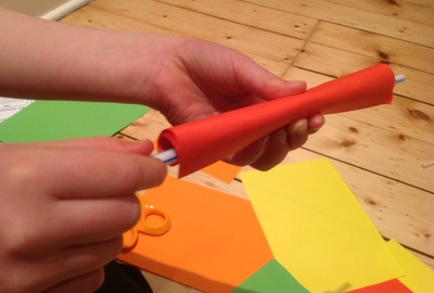 Coloured paper, straw, paper wrapped round straw, hands