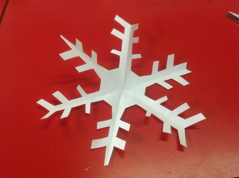 Cutout snowflake, red table, white paper  - Cut-out Snowflakes