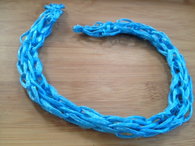 finger knitting with blue plastic yarn