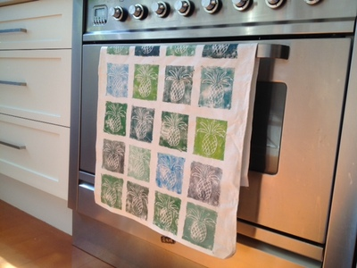 hand printed tea towel, tea towel hanging on cooker, printed tea towel, how to print on a tea towel, hand printed dish cloth, printing on fabric tutorial, cheap gift idea for grandparents, easy homemade gift to post