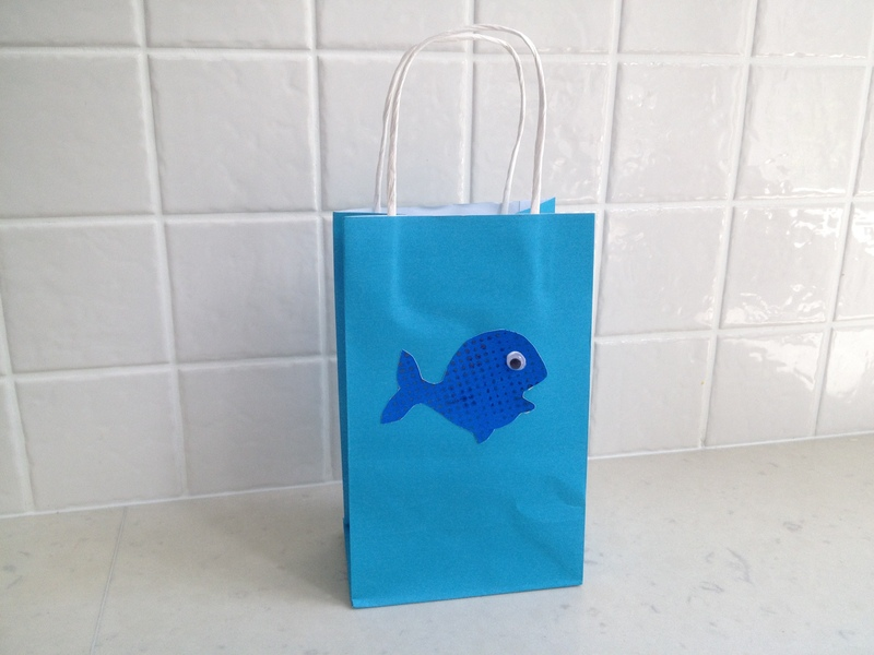 using a cookie cutter to trace a fish shape, whale, fish, fish outline, whale outline  - Decorated Party Bag