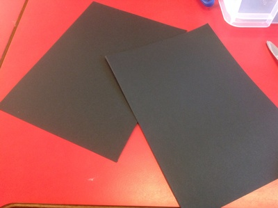 Sheets of black card, red table