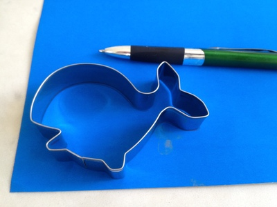 using a cookie cutter to trace a fish shape, whale, fish, fish outline, whale outline